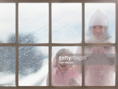 Girls looking in through frosty windows : Stock Photo