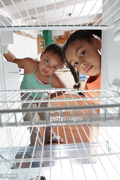 Girls looking into empty fridge