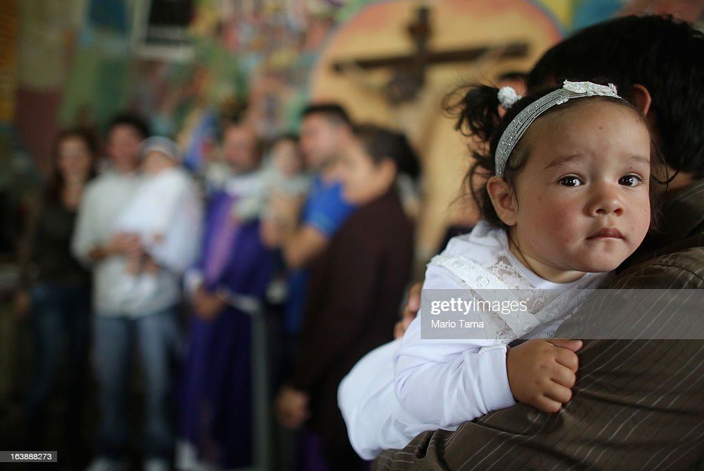 A girls looks on after her baptism ceremony in the Virgin of the Miracles of Caacupe church following Sunday Mass in the Villa 21-24 slum, where archbishop Jorge Mario Bergoglio, now Pope Francis, used to perform charity work, on March 17, 2013 in Buenos Aires, Argentina. Francis was the archbishop of Buenos Aires and is the first Pope to hail from South America. Some locals are now affectionately calling Francis, known for his charity work in the slums, the 'slum pope.'