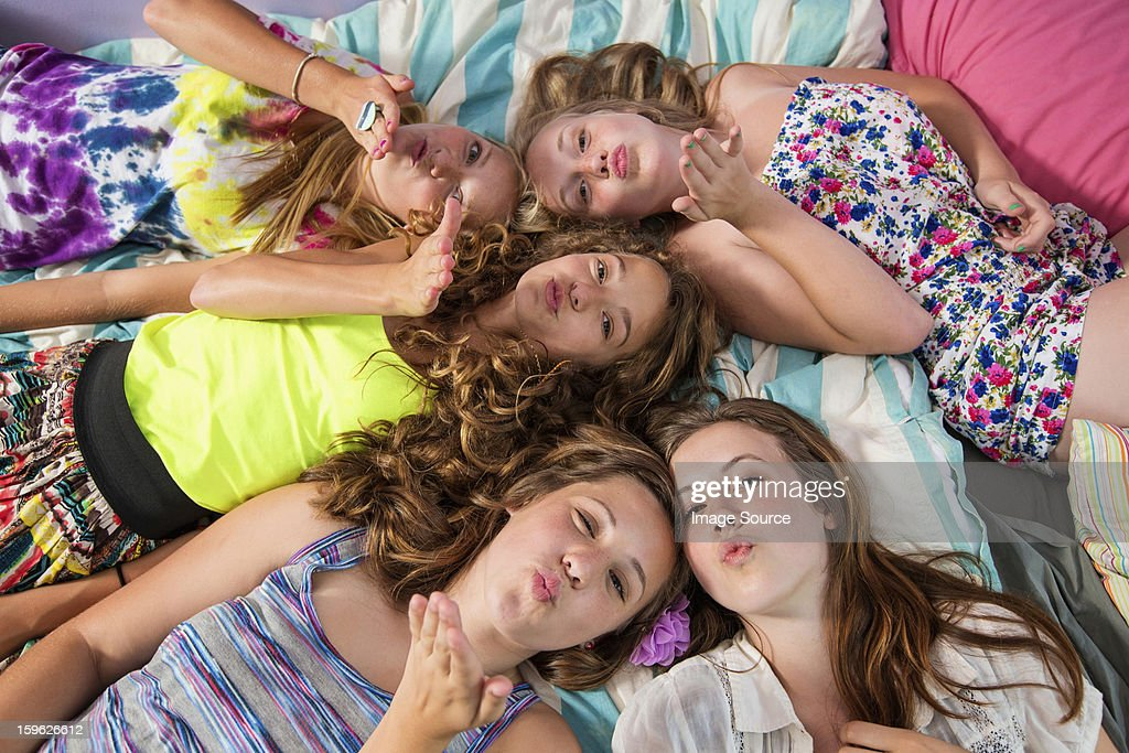 Girls lying on bed, blowing kisses : Stock Photo