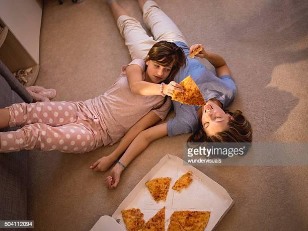 Frauen liegen auf dem Boden in einigen take-away-pizza