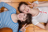 Girls lying on wooden floor doing peace signs