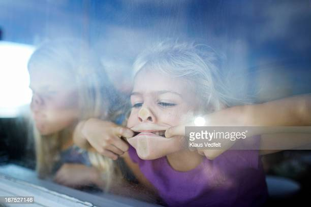 Girls making funny faces behind window