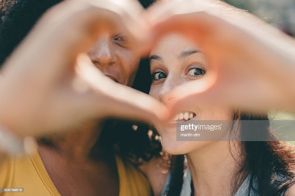 Girls making heart shaped symbol with hands : Stock Photo