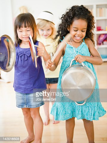 Girls making music with pots and pans : Stock Photo
