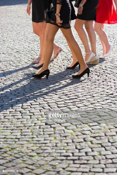 Girls' night out bare legs high heels and miniskirts short skirts of young ladies in hen party girl power group on cobble stones in Bruges Belgium