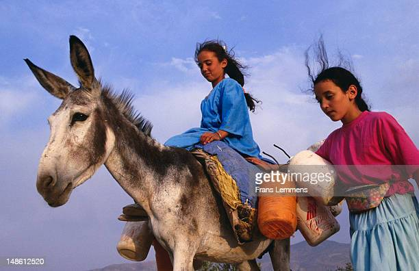 Girls of Berber tribe with donkey transporting water.