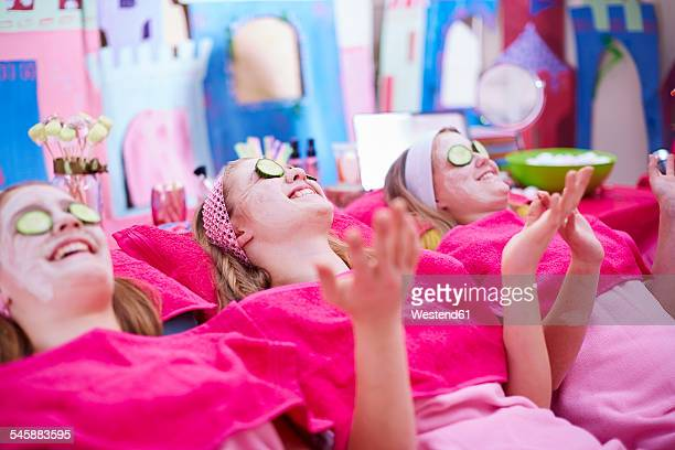 Girls on a beauty farm with cucumber facial masks