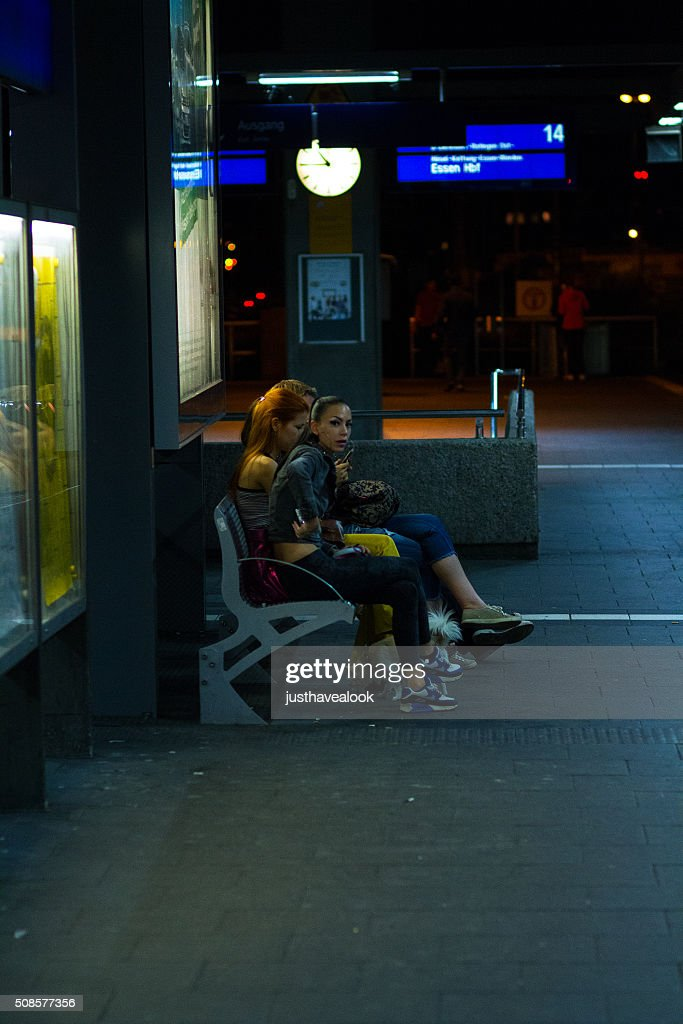 Girls on bench in station at summer night : Stock Photo