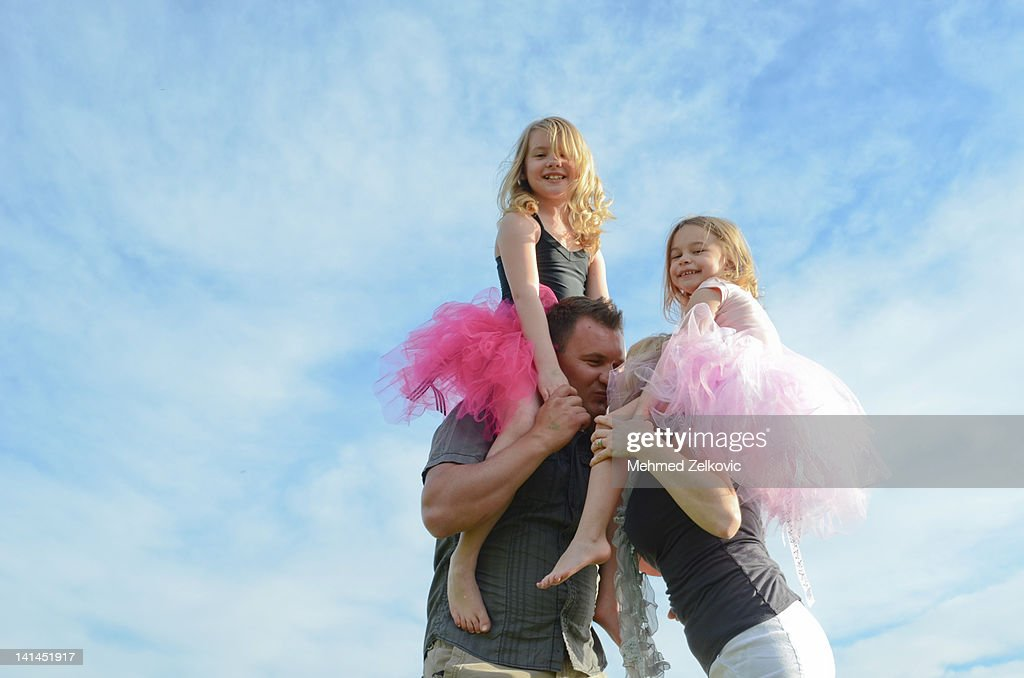 Girls on shoulder of parents : Stock Photo