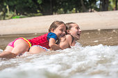 Two little girls having fun on the beach in the water.