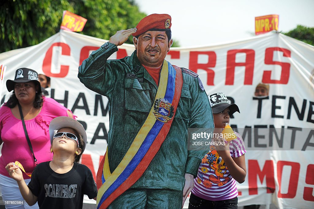 Girls participate in a traditional May Day rally with a life-size figure of the late president of Venezuela, Hugo Chavez, in San Salvador, on May 1, 2013. AFP PHOTO/ Jose CABEZAS