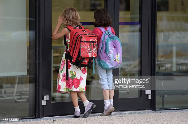 Girls peek into a classroom at the European school of Strasbourg in Strasbourg eastern France on September 1 the first day of the new school year AFP...