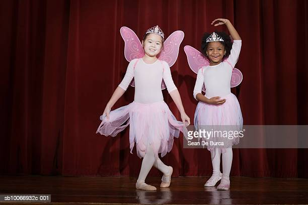 Girls (6-9) performing ballet on stage, smiling