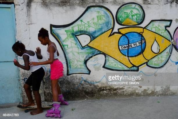 Girls play at the Cidade de Deus shantytown in Rio de Janeiro on January 23 2014 AFP PHOTO / Christophe Simon
