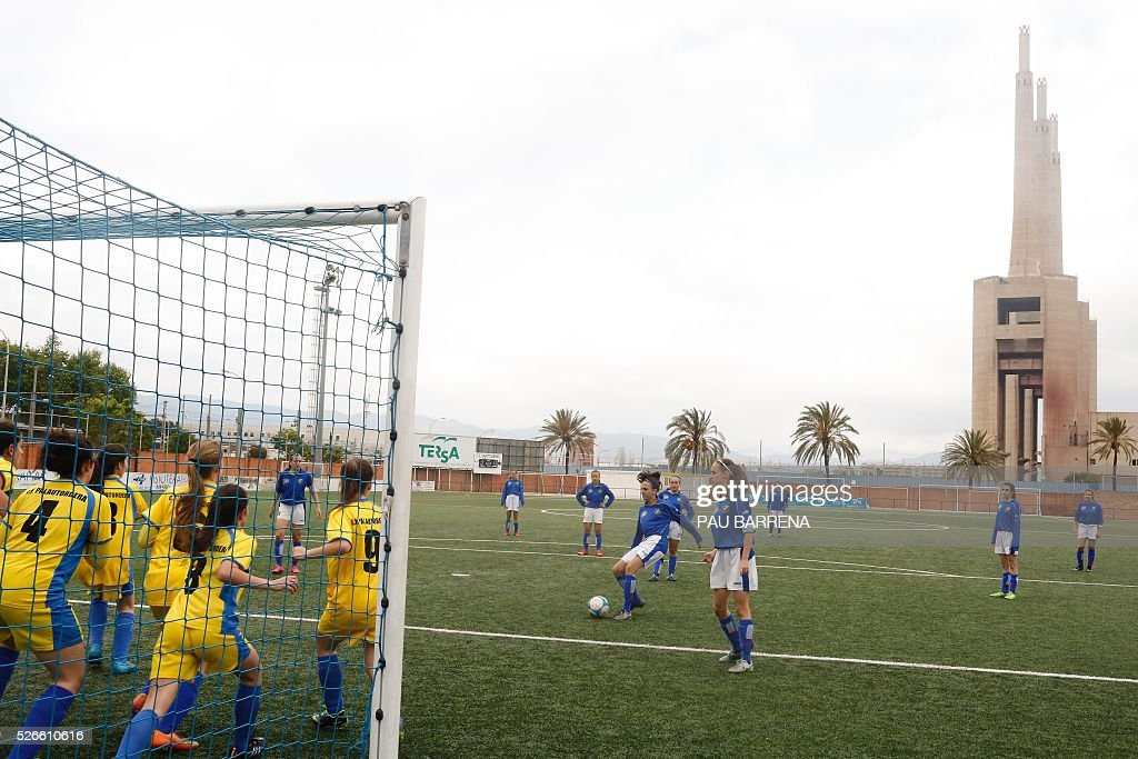 Girls play during an amateur football match in Sant Adria del Besos, near Barcelona, on a pitch located next to a non-functional thermal central. / AFP / PAU