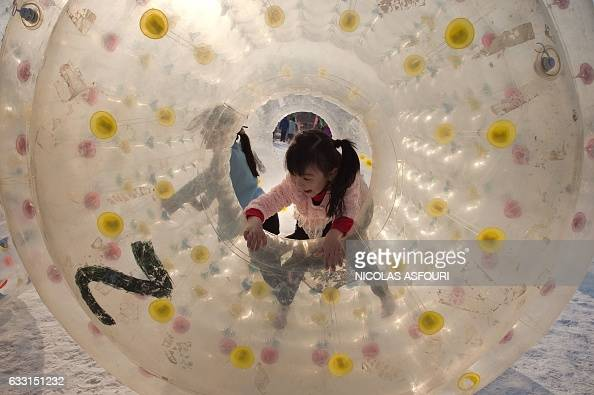 Girls play inside an inflated device at an amusement fair in a park during the Spring Festival holidays in Beijing on January 31 2017 Millions of...