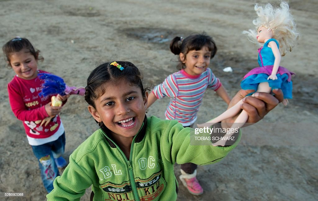 Girls play with a doll at a makeshift camp for migrants and refugees near the village of Idomeni not far from the Greek-Macedonian border on April 30, 2016. Some 54,000 people, many of them fleeing the war in Syria, have been stranded on Greek territory since the closure of the migrant route through the Balkans in February. / AFP / TOBIAS