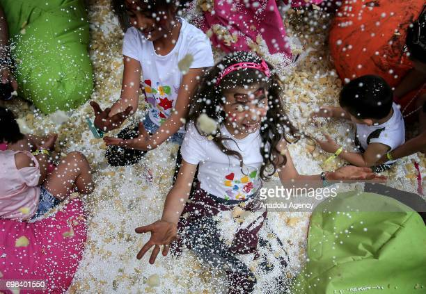 Girls play with confetti during the World Refugee Day celebrations which is held by the UN Refugee Agency at Veliefendi Race Course in Istanbul...