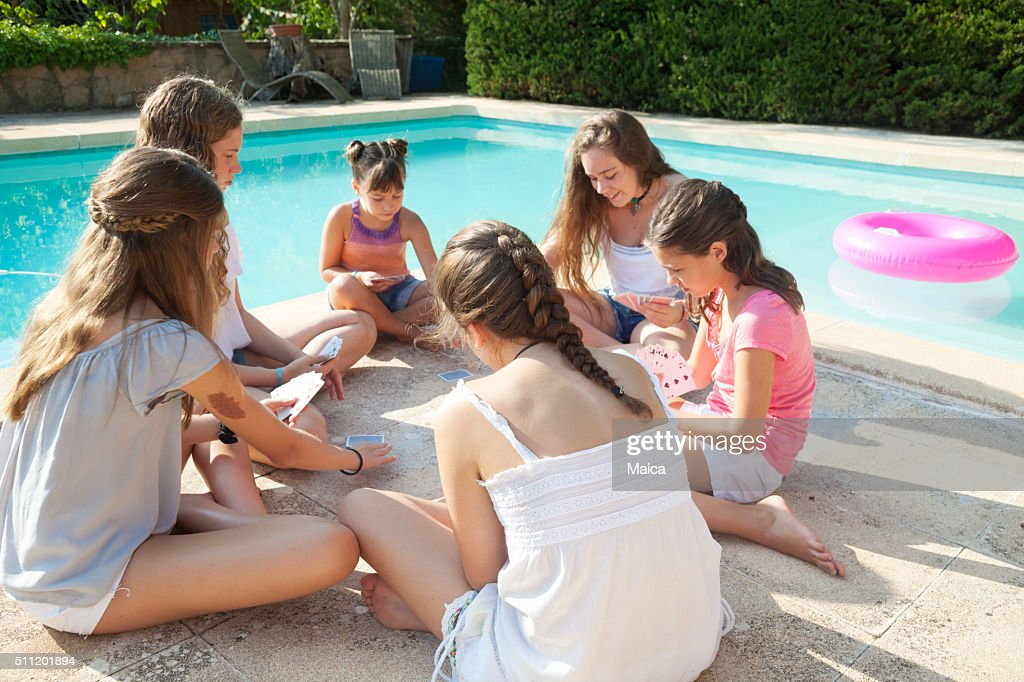 Girls playing cards in sumer by a pool