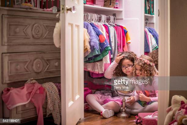 Girls playing dress up and applying makeup in mirror