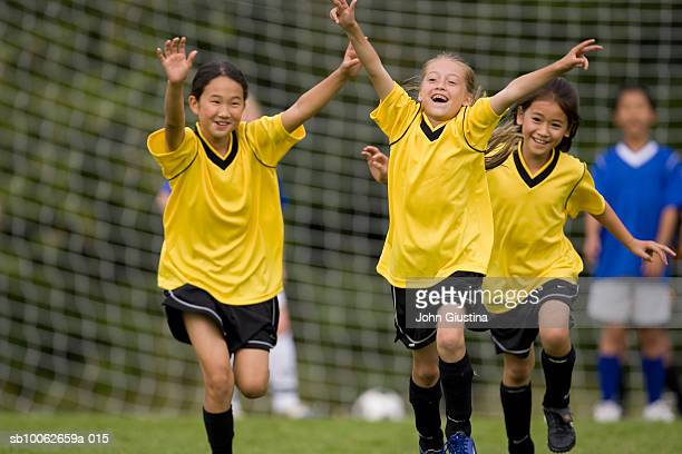 Girls (8-11) playing football (differential focus)