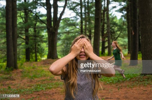 Girls playing hide and seek in a pine forest.