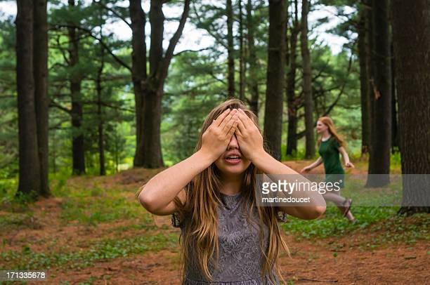 Niñas jugar al escondite en un bosque de pinos.