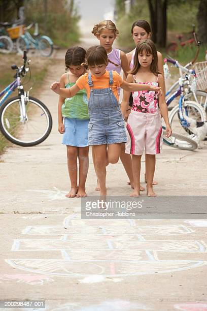 Girls (6-12) playing hopscotch