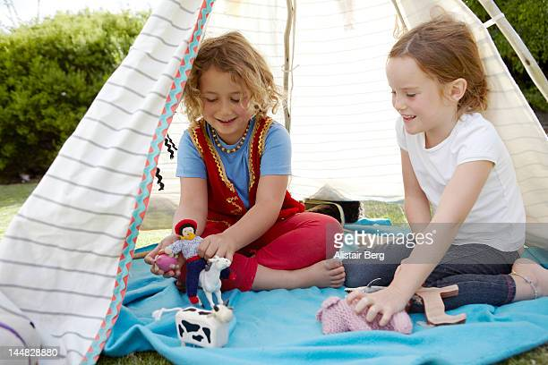 Girls playing in a tent