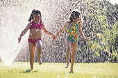 Girls Playing in Sprinkler