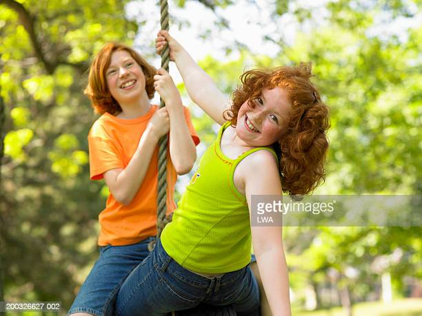 Girls (10-12) playing in tire swing outdoors, portrait