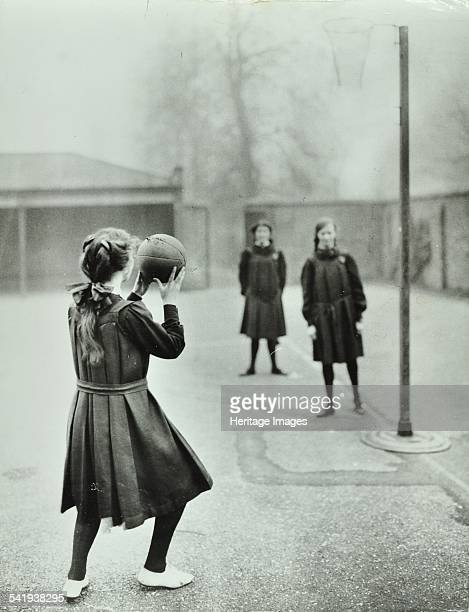 Girls playing netball Chelsea Secondary School London 1911 A girl is poised ready to shoot a goal Artist unknown