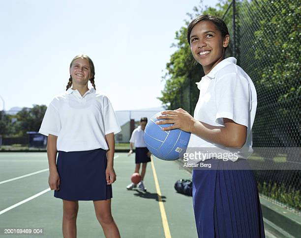 Girls (12-14) playing netball, smiling, low angle view