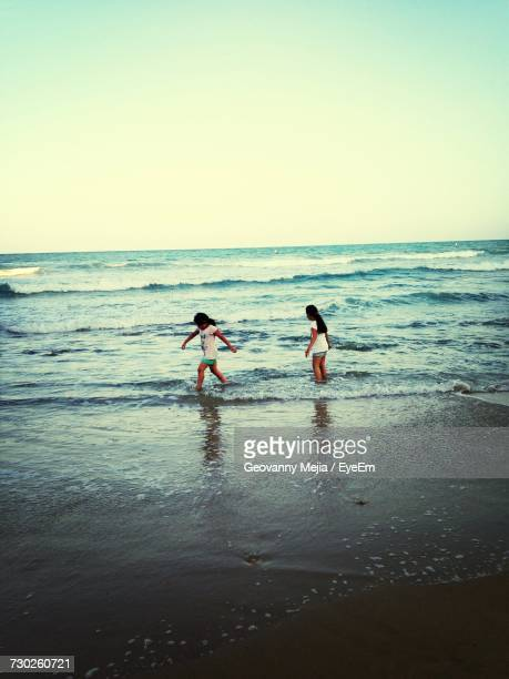 Girls Playing On Shore At Beach Against Clear Sky