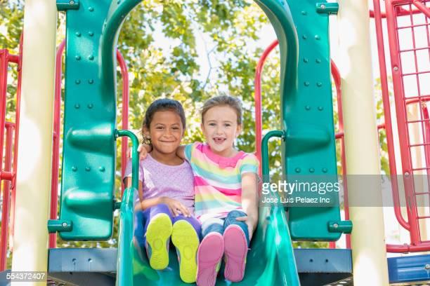 Girls playing on slide at playground