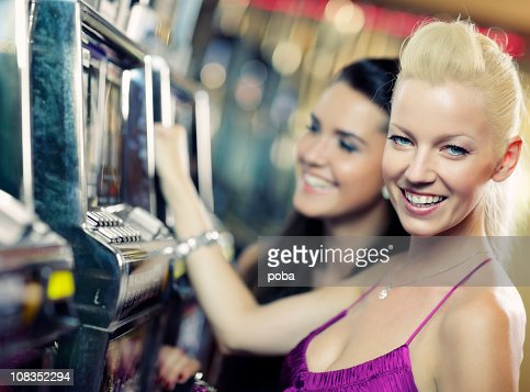 girls playing on slot machine : Stock Photo