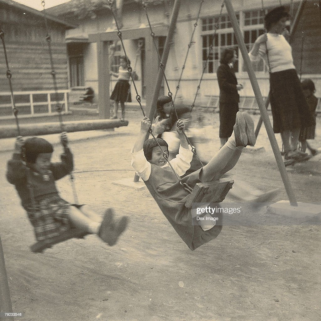 Girls playing on swings in a playground : Stock Photo