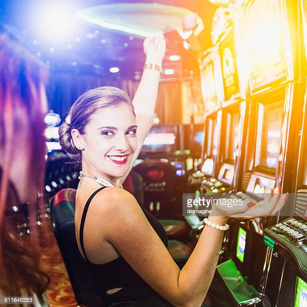 Girls playing slot machine in the casino