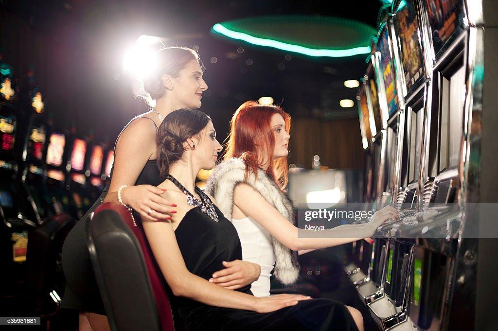 Girls playing slot machine in the casino : Stock Photo