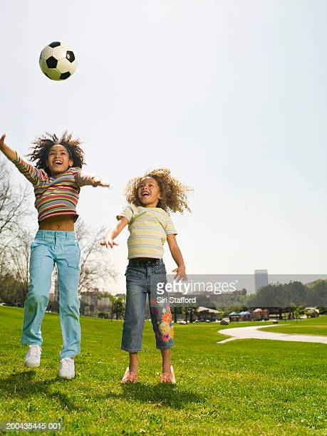 Girls (4-9) playing soccer in park