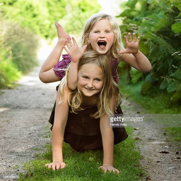 Girls playing together on dirt path