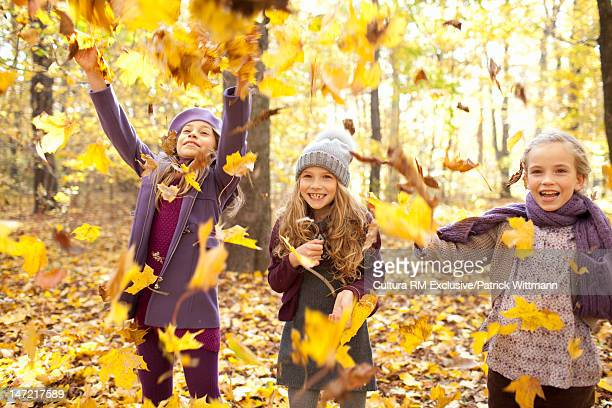 Girls playing with autumn leaves