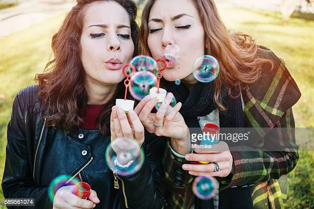 Girls playing with bubbles in the park
