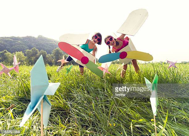 Girls playing  with cardboard airplanes