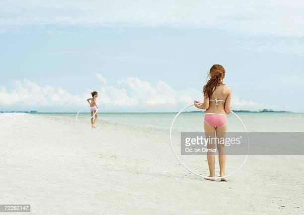Girls playing with hoola hoops on beach
