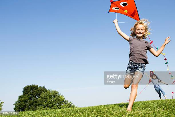 Girls playing with kites outdoors