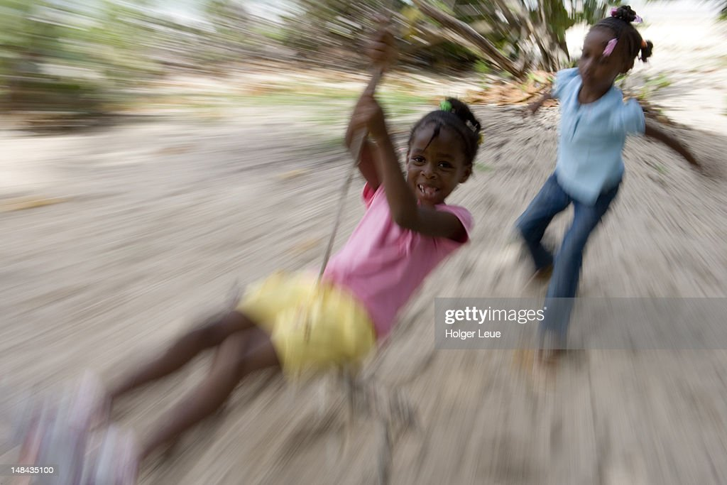 Girls playing with rope swing, Paradise Beach. : Stock Photo