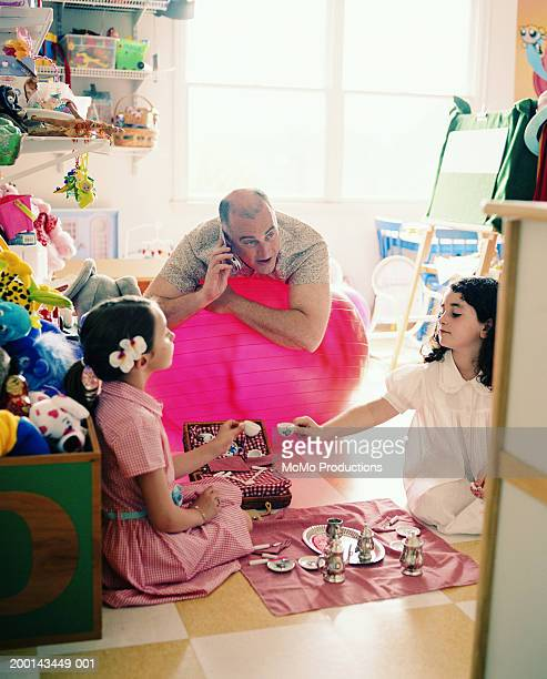 Girls (5-8) playing with toy tea set, father using mobile phone