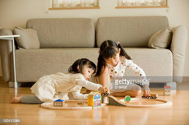 Girls playing with toy trains at living room.